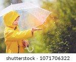 happy kid catching rain drops... | Shutterstock . vector #1071706322