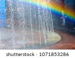 Small photo of Close up of beautiful city fountain. Splashing upward crystal thin streams of clear cool transparent water, shiny droplets. Multicolored blurred rainbow, recreation area.