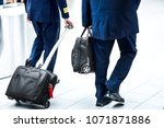 pilots pull or carry suitcases... | Shutterstock . vector #1071871886