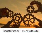 gears in the hands of a team of ... | Shutterstock . vector #1071936032
