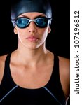 Female swimmer wearing goggles and hat - isolated over a black background - stock photo