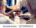 group of people holding hands... | Shutterstock . vector #1072003412