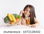 happy little girl eating fresh...   Shutterstock . vector #1072128332