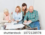 Small photo of Family with seniors solve puzzles as memory training against dementia