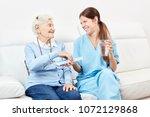 smiling senior woman receives a ... | Shutterstock . vector #1072129868