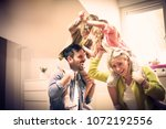 parents carrying daughters on... | Shutterstock . vector #1072192556