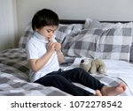 Small photo of Cute little boy trying to close white polo shirt buttons, School Kid sitting in bed with teddy bear tried to button up his school polo shirt, Cute boy getting dressed and get ready for school