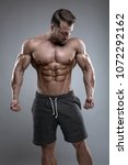 Small photo of Strong Athletic Man shows body and abdominal muscles over gray background