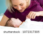 beautiful blond mother with her ... | Shutterstock . vector #1072317305