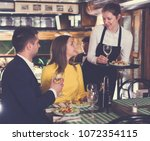 woman waiter is brings order to ... | Shutterstock . vector #1072354115