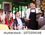 man waiter is brings order to... | Shutterstock . vector #1072354148