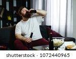 fat man drinks beer lying on...   Shutterstock . vector #1072440965