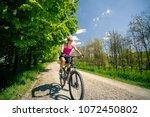 woman cycling a mountain bike... | Shutterstock . vector #1072450802