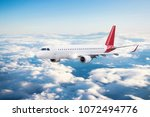 airplane over the clouds | Shutterstock . vector #1072494776