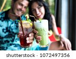 young happy couple cheers on... | Shutterstock . vector #1072497356