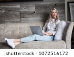 young woman sitting with laptop | Shutterstock . vector #1072516172