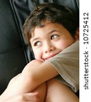 Small photo of Cute little boy smiles cheekily and he jokes with family.