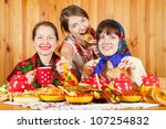 Women in traditional clothes celebrating Shrovetide and eats pancake - stock photo