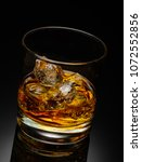 Small photo of Glass of scotch whiskey with ice cube on a black background