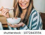 crop woman close up eating oat... | Shutterstock . vector #1072663556