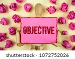 Small photo of Handwriting text Objective. Concept meaning Goal planned to be achieved Desired target Company mission written Sticky Note paper holding by Wooden Robot Toy plain background Paper Balls.