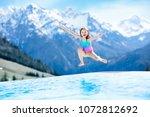 child in outdoor infinity pool... | Shutterstock . vector #1072812692