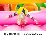 Small photo of Child jumping on colorful playground trampoline. Kids jump in inflatable bounce castle on kindergarten birthday party Activity and play center for young child. Little boy playing outdoors in summer.