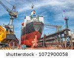 a cargo ship in dry dock | Shutterstock . vector #1072900058