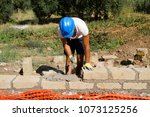 bricklayer building a new wall | Shutterstock . vector #1073125256