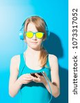 Small photo of Teenager with ponytail wearing sunglasses and blue headphones listening to music with smartphone on blue backdrop.