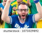 "Small photo of Group of fans cheer for brazilian team on stadium bleachers. Emotions portrait. Goal, victory, celebration. Man wearing generic brandless blue t-shirt written ""Brasil"" (Brazil in portuguese)."
