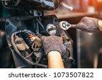 motorcycle mechanic using a... | Shutterstock . vector #1073507822