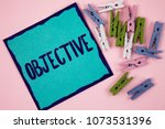 Small photo of Handwriting text writing Objective. Concept meaning Goal planned to be achieved Desired target Company mission written on Sticky note paper on plain Pink background Wooden Clips next to it.