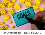 Small photo of Word writing text Goals. Business concept for Desired Achievements Targets What you want to accomplish in the future written by Man on Sticky note paper holding Marker plain background Paper Balls.