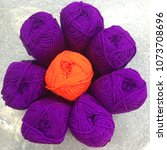 Small photo of One orange yarn with many purple yarns , differences concept