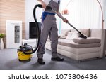 man cleaning sofa in the living ...   Shutterstock . vector #1073806436