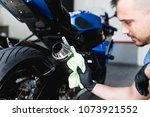 a man cleaning motorcycle with... | Shutterstock . vector #1073921552