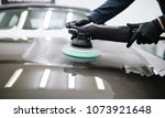 Small photo of Car detailing - Man with orbital polisher in repair shop polishing car. Selective focus.