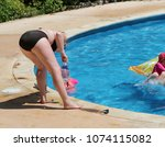 woman near a pool with kids.   Shutterstock . vector #1074115082
