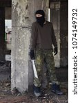 Small photo of Masked man with machete, in ruined building, hiding behind the wall