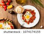shakshouka  dish of eggs... | Shutterstock . vector #1074174155