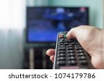 a hand with a remote control... | Shutterstock . vector #1074179786