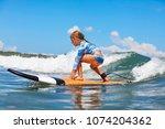 happy baby girl   young surfer... | Shutterstock . vector #1074204362