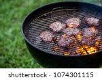 beef hamburgers cooking on a... | Shutterstock . vector #1074301115