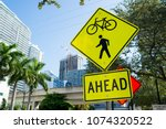 Small photo of Traffic signs on city road in miami, usa. Bicycle and pedestrian crossing ahead warning. Transportation traffic and travel. Caution and warn concept.