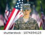 Beautiful American soldier looking into the camera. American flags as background - stock photo