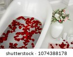 white bath with rose petals.... | Shutterstock . vector #1074388178