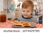 little boy having breakfast... | Shutterstock . vector #1074429785