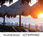 sun loungers sit under a palm... | Shutterstock . vector #1074490382