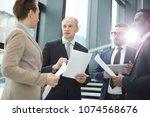 mature leader of business group ... | Shutterstock . vector #1074568676